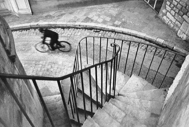 The cyclist caught gliding down a cobbled hill. Henri  Cartier-Bresson